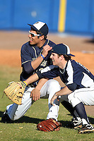 Pittsburgh Panthers Alex Caravella #32 (left) and Matt Iannazzo #23 (catching) joke around before a game vs. the Central Michigan Chippewas at Chain of Lakes Park in Winter Haven, Florida;  March 11, 2011.  Pittsburgh defeated Central Michigan 19-2.  Photo By Mike Janes/Four Seam Images