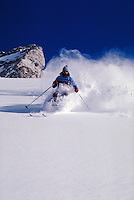 Incredibly light powder sprays up the chest of a skier as he cuts through it on a cold, crisp day on an open slope. Ray Nelson. Utah, Alta Ski Resort.