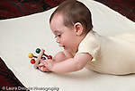 5 month old baby girl on stomach, closeup, grasping toy