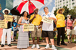 July 13, 2015. Winston Salem, North Carolina.<br /> (left to right) Brenda Chisholm, Monroe Miles and David Marshburn show their support for the NC NAACP's lawsuit against Gov. Pat McCrory.<br />  To rally support for the North Carolina NAACP's case against Gov. Pat McCrory (NC NAACP v. McCrory), a march was held in downtown Winston Salem on the opening day of the case in federal court. Thousands gathered to walk the streets of downtown and listen to speeches proclaiming the importance of defeating new requirements for voter registration,<br />  The NC NAACP contests that HB 589 (Voter ID requirements) violate Section 2 of the Voting Rights Act (42 U.S.C. 1973) and the Fourteenth and Fifteenth Amendments of the Constitution.