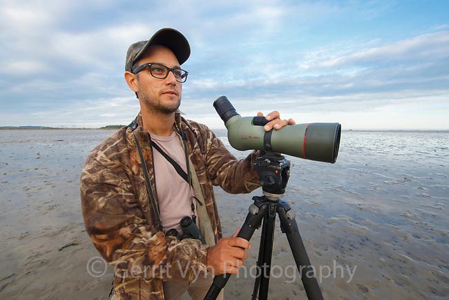 Birder looking for shorebirds on mudflats in South Korea. October.