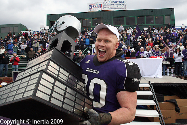 ROME, GA - DECEMBER 19:  Brandon Koolstra #90 of the University of Sioux Falls grabs the championship trophy after the Cougars defeated Lindenwood University 25-22 in the NAIA Championship game Saturday afternoon at Barron Stadium in Rome, GA. (Photo by Dave Eggen/Inertia)
