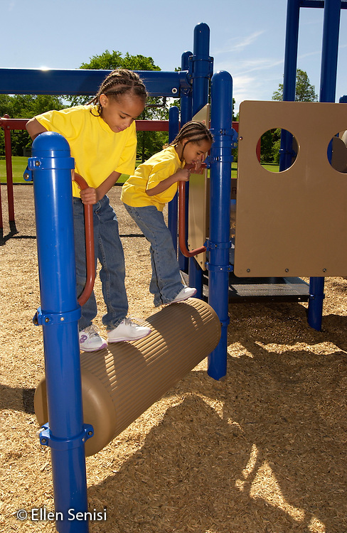 MR/Schenectady, NY.Zoller Public School Playground.Girls (7, African American and Caucasian, Fraternal twins) play on rolling tube on playground..MR: Puc1  Puc2  .©Ellen B. Senisi