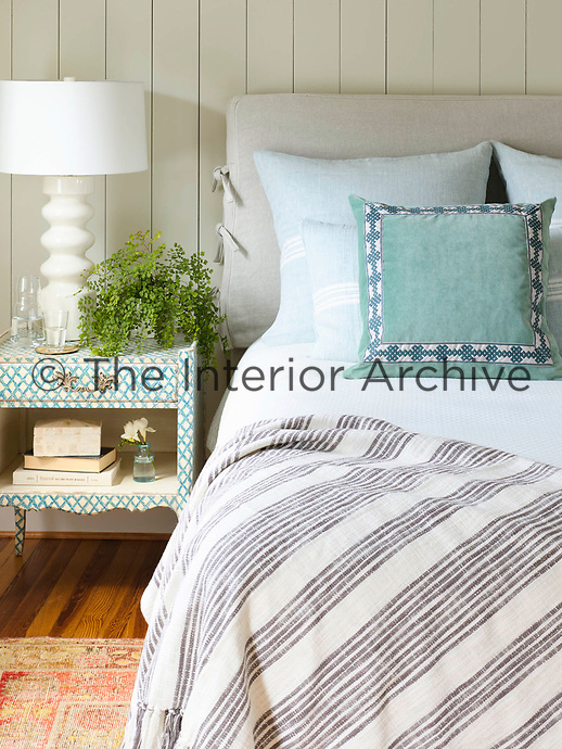 In the bedroom, the double bed has a grey upholstered headboard and bedside lamp on a blue bedside cabinet. A grey and white striped cover is draped across the bed.