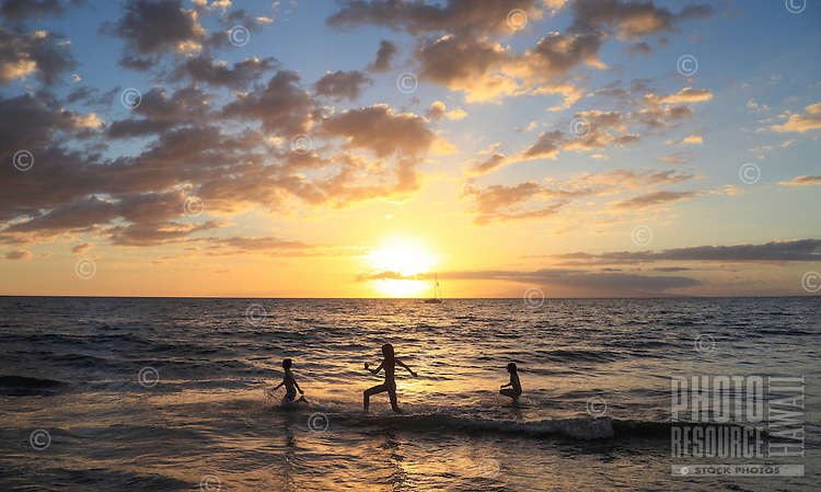Children running into the ocean are silhouetted by the setting sun at a beach in Kihei, Maui.