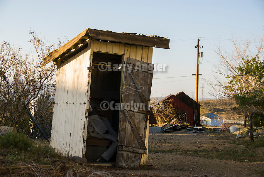 White painted wooden outhouse with open door and dummy, Randsburg, Calif.