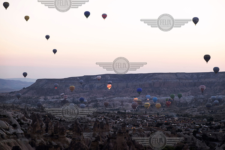 Hot air balloons flying in the early morning above the ancient village of Goreme.