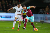 Jack Cork of Swansea City and Mauro Zarate of West Ham United in action during the Barclays Premier League match between Swansea City and West Ham United played at The Liberty Stadium, Swansea on 20th December 2015