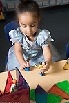 Education Preschool 2-3 year olds girl in dressup dress playing with dolls and magnetic tiles construction