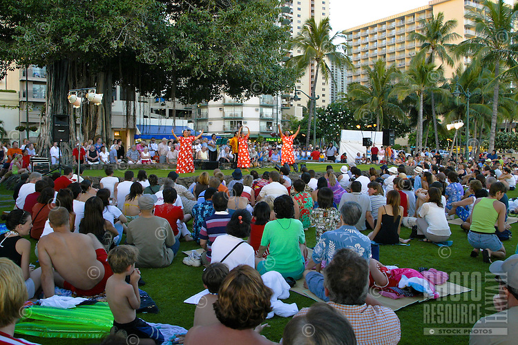 Tourist enjoy watching Hula Dancers of all ages perform at the Kuhio Beach Park stage under the Banyan Tree. A variety of music/chant and dance is performed at this weekly event. Located near Waikiki Beach, Oahu.