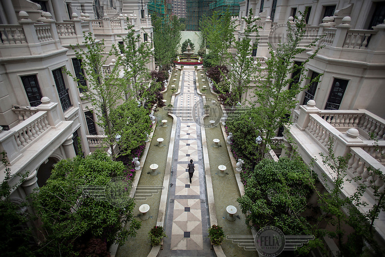 A woman walks through the completed gardens at the Yulong Palace real estate development.