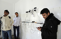 Pictured: Refugee men check on their mobile phones that are left charging in a room Friday 26 February 2016<br /> Re: Hundreds of refugees have been given temporary shelter at the Stefanakis Army Camp in the Schisto area of Athens, Greece.