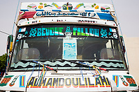"Senegal, Touba.  Inter-city transport bus.  ""Alhamdoulilahi"" is Arabic for ""Praise be to God."" an expression of thanksgiving.  The photo on the windshield and other markings identify the vehicle owner or driver as a member of the Mouride Islamic brotherhood."