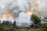 Pictured: Firemen battle with the flames in Varnavas, near Kalamos.<br /> Re: A forest fire has been raging in the area of Kalamos, 20 miles east of Athens in Greece. There have been power cuts, country houses burned and children camps evacuated from the area.
