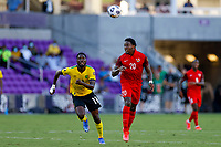 July 16th 2021; Orlando, Florida, USA; Jamaica forward Shamar Nicholson (11) and Guadeloupe defender Stevenson Casimir (20) challenge for the ball during the Concacaf Gold Cup match between Guadeloupe and Jamaica on July 16, 2021 at Exploria Stadium in Orlando, Fl.