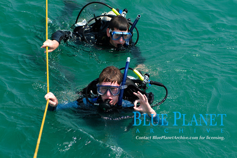 Two divers coming back to the boat at the surface and doing OK. Two divers, teenagers, swimming surface, doing the OK sign, snorkel, regulator, tank, scuba diving, safety sign, hanging a rope, off Texas coast, Gulf of Mexico, South Padre Island, South Texas, USA