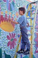 HISPANIC BOY PAINTS ON WALL MURAL AS PART OF PROJECT TO IRRADICATE GRAFFITI IN BARRIO. HISPANIC ELEMENTARY SCHOOL AGE BOY. SAN ANTONIO TEXAS.