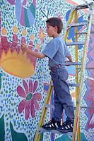 HISPANIC BOY PAINTS ON WALL MURAL AS PART OF PROJECT TO IRRADICATE GRAFFITI IN BARRIO. HISPANIC ELEMENTARY SCHOOL AGE BOY. SAN ANTONIO TEXAS.