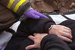 A firefighter comforting a patient that was carried in a carry blanket out of an emergency scene