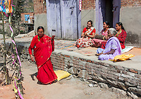 Bhaktapur, Nepal.  Middle-aged Woman Dances while Friends Play Drum and Clap while Sitting on Front Forch of their House.