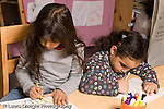 Education Preschool 3-4 year olds art activity two girls sitting side by side drawing with markers horizontal