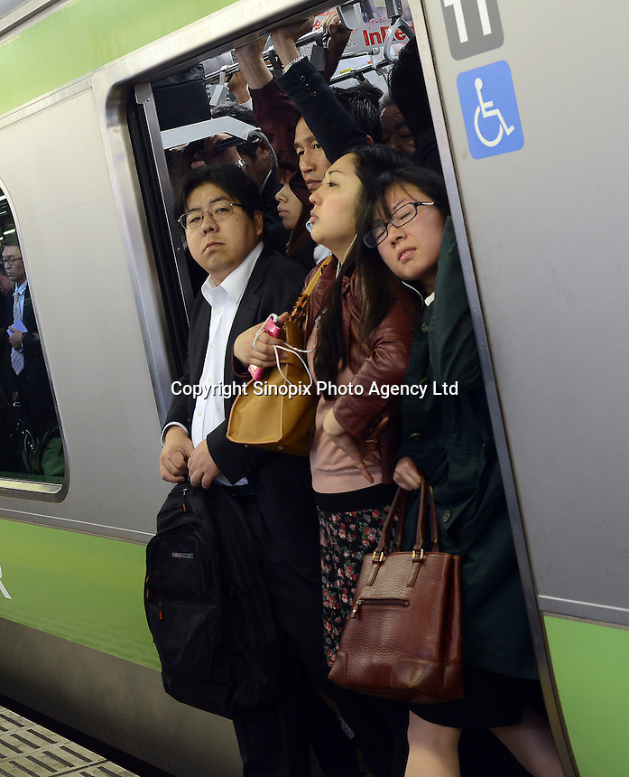 Passengers squeeze onto already full trains during morning rush hour, Shinjuku Station, Tokyo. With up to 4 million passengers passing through it every day, Shinjuku station, Tokyo, Japan, is the busiest train station in the world. The station was used by an average of 3.64 million people per day.  That's 1.3 billion a year.  Or a fifth of humanity. Shinjuku has 36 platforms, and connects 12 different subway and railway lines.  Morning rush hour is pandemonium with all trains 200% full. <br /> <br /> Photo by Richard jones / sinopix