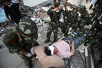 Soldiers move a survivor pulled from the rubbles in Beichuan, Sichuan, China. China now estimates the death toll to be around 50,000 as prospects of survival for those still buried diminishes..15 May 2008