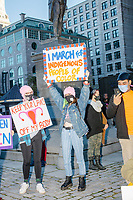 """Protestors gather near the statue of Samuel Adams outside Faneuil Hall at the end of the 2020 Women's March protest in opposition to the re-election of US president Donald Trump in Boston, Massachusetts, on Sat., Oct. 17, 2020.<br /> The signs here read """"My body / My choice,"""" """"I march for indigenous people of color,"""" """"Trans women are women,"""" """"Keep your hands off my body,"""" and """"Uphold Obergefell v. Hodges,"""" a reference to the landmark Supreme Court Case making same-sex marriage legal in the United States."""
