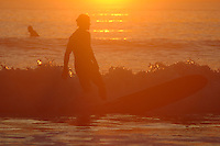 Pacific Beach, San Diego, California, USA:  Monday, January 19 2009.  A surfer kicks out of a wave just off the beach at the bottom of Loring Street as the sun sets in the background.  The Martin Luther King Jnr Day holiday was marked by warm weather, big surf and a technicolored sunset as much of the rest of the country shivered in the cold.