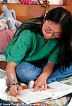 12 year old adolescent girl sitting on bed doing homework vertical Asian Korean American