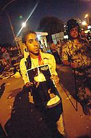 EGITTO, IL CAIRO 9/10 settembre 2011: assalto all'ambasciata israeliana. Migliaia di manifestanti egiziani, ancora infuriati per l'uccisione di cinque guardie di frontiera egiziane da parte dell'esercito israeliano, hanno fatto irruzione nella sede diplomatica israeliana e sono stati poi sgomberati da esercito e polizia egiziana. Nell'immagine: un giovane manifestante mostra la fotografia di un uomo. Dietro di lui un poliziotto e altri manifestanti la sera degli scontri.<br /> Egypt attack to the Israeli embassy  Attaque à l'ambassade israelienne Caire