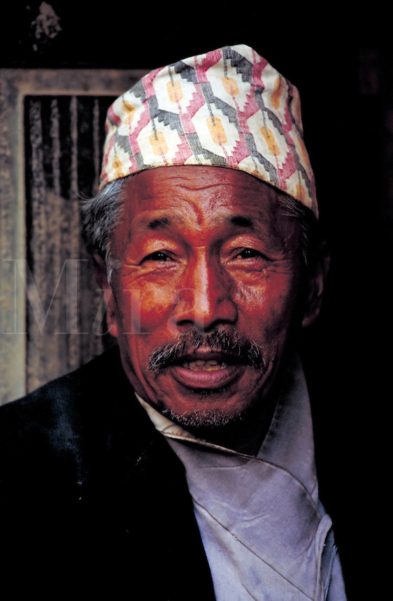 Smiling middle-aged man with mustache and wearing a topi; full-face; head and shoulders. Kathmandu, Nepal.