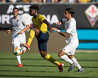 CHARLOTTE, NC - JULY 20: Bukayo Saka #77 is chased by Lorenzo Venuti #2 during a game between ACF Fiorentina and Arsenal at Bank of America Stadium on July 20, 2019 in Charlotte, North Carolina.