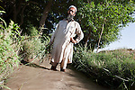 31 May 2013, 310513 Shikhano Village, Surkhrod District , Jalalabad, Afghanistan.    Nazir of Shikhano Village, Surkhrod District, who is responsible for the canal system in his village and when water is diverted and directed stands in one of the waterways.  Canals are being built and rehabilitated under the Irrigation Restoration and Development Project (IRD). While some donors are supporting reconstruction/development of specific rivers the Emergency Irrigation Rehabilitation Project (EIRP) is instrumental in the Govt of Afghanistan's launch of a national irrigation scheme. Typical rehabilitation works would include improving canal intake structures, conveyance channels and aqua ducts. Picture by Graham Crouch/World Bank