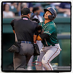 Nick Gonzales (2) of the Greensboro Grasshoppers slams into home plate umpire Ray Valero while scoring a run in a game against the Greenville Drive on Tuesday, July 20, 2021, at Fluor Field at the West End in Greenville, South Carolina. (Tom Priddy/Four Seam Images)
