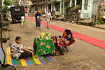 Residents of the 7th street lay out the red carpet in preparation for the visit by Buddhist monks from a local monastery.  Yangon Rangoon, Myanmar Burma 2008.