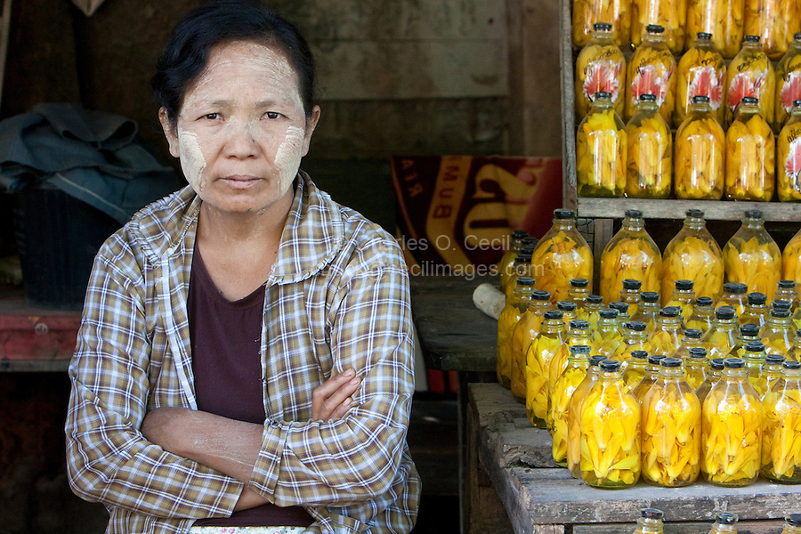 Myanmar, Burma, near Bagan.  Burmese Woman Selling Magnolia  Petals, given as gifts to Buddha.  She is wearing thanaka paste on her face as a cosmetic sunscreen.
