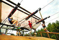 Participants end their flight on the MegaZip line. Riders took flight, zooming through the air over the US National Whitewater Center (USNWC) on the USNWC's zip-lines, part of the facilities high-adventure offerings. The popular outdoor adventure activity lets outdoor enthusiasts be secured into a harness then propelled by gravity along an inclined steel cable. Charlotte, North Carolina's US National Whitewater Center offers multiple zip line courses, which vary in height and distance traveled, as well as one of the largest outdoor climbing facilities in the world. The USNWC is a non-profit outdoor recreation facility open to the public for whitewater rafting, kayaking, canoeing, rappelling, zip lining, mountain biking, hiking, climbing and more. The center opened to the public in 2006.