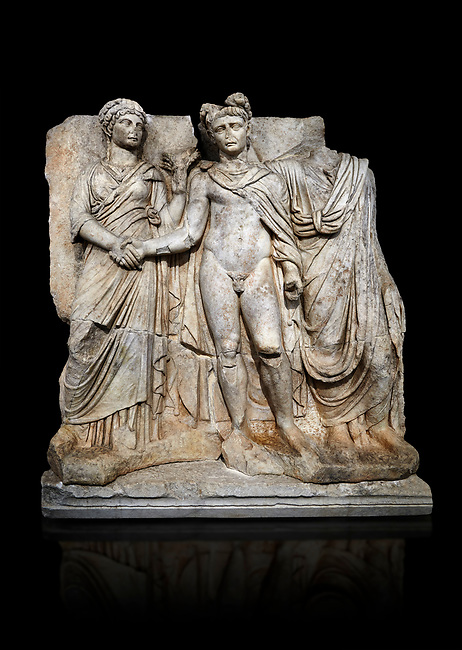 """Roman Sebasteion relief sculpture of emperor Claudius and Agrippina, Aphrodisias Museum, Aphrodisias, Turkey.   Against a black background.<br /> <br /> Claudius in heroic nudity and military cloak shakes hands with his wife Agrippina and is crowned by the Roman people or the Senate wearing a toga. The subject is imperial concord with the traditional Roman state. Agrippina holds ears of wheat: like Demeter goddess of fertility. The emperor is crowned with an oak wreath, the Corona civica or """"citizen crow"""", awarded to Roman leaders for saving citizens lives: the emperor id therefore represented as saviour of the people."""