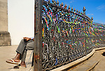 Brazil, Bahia, Salvador: Handicapped person tactfully collecting money at the church gate to Igreja do Bonfim (1754) on Salvador's peninsula Itapagipe. Colorful miracle ribbons decorating the fencing of the church. The fita, or miracle ribbons, of Senhor do Bonfim comes in many colors and is nomally tied around a persons wrist. Its primary function is to petition for future miracles rather than to remind anyone of previous such interventions. The fita is also worn to promote Brazilian pride or as a souvenir by tourists. --- No signed releases available.