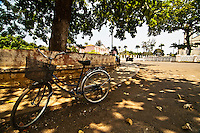 an old bicycle with its basket parked under the shade of a big ecuatorial tree in a roundabout of the capital, Sao Tomé