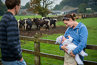 """A mother breastfeeding her baby of a few months at a visitor farm park with cows in the background and her husband beside her.<br /> <br /> Image from the breastfeeding collection of the """"We Do It In Public"""" documentary photography picture library project: <br />  www.breastfeedinginpublic.co.uk<br /> <br /> <br /> Gloucestershire, England, UK<br /> 30/09/2013<br /> <br /> © Paul Carter / wdiip.co.uk"""