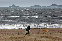 Pictured: A man walks his dog on the beach overlooking the village of Mumbles, Swansea, Wales, UK. Thursday 20 September 2018<br /> Re: Heavy rain and strong winds brought by Storm Bronagh has hit parts of the UK.