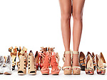Closeup of young woman legs surrounded by several pairs of different fashionable shoes isolated on white background Image © MaximImages, License at https://www.maximimages.com