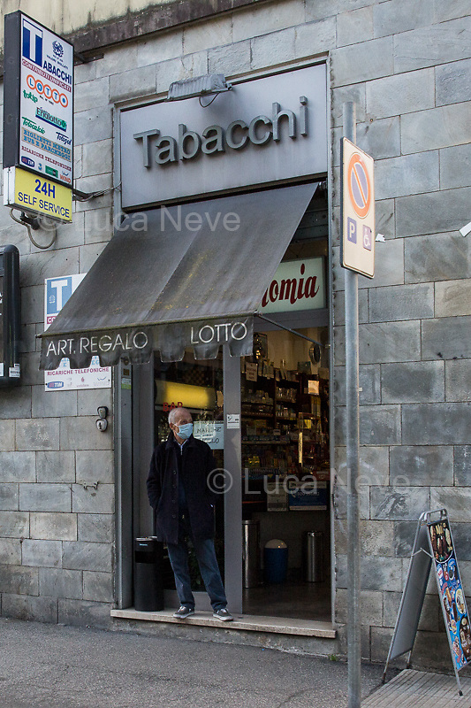 """Tobacco shop: open.<br /> <br /> Rome, 12/03/2020. Documenting Rome under the Italian Government lockdown for the Outbreak of the Coronavirus (SARS-CoV-2 - COVID-19) in Italy. On the evening of the 11 March 2020, the Italian Prime Minister, Giuseppe Conte, signed the March 11th Decree Law """"Step 4 Consolidation of 1 single Protection Zone for the entire national territory"""" (1.). The further urgent measures were taken """"in order to counter and contain the spread of the COVID-19 virus"""" on the same day when the WHO (World Health Organization, OMS in Italian) declared the coronavirus COVID-19 as a pandemic (2.).<br /> ISTAT (Italian Institute of Statistics) estimates that in Italy there are 50,724 homeless people. In Rome, around 20,000 people in fragile condition have asked for support. Moreover, there are 40,000 people who live in a state of housing emergency in Rome's municipality.<br /> March 11th Decree Law (1.): «[…] Retail commercial activities are suspended, with the exception of the food and basic necessities activities […] Newsagents, tobacconists, pharmacies and parapharmacies remain open. In any case, the interpersonal safety distance of one meter must be guaranteed. The activities of catering services (including bars, pubs, restaurants, ice cream shops, patisseries) are suspended […] Banking, financial and insurance services as well as the agricultural, livestock and agri-food processing sector, including the supply chains that supply goods and services, are guaranteed, […] The President of the Region can arrange the programming of the service provided by local public transport companies […]».<br /> Updates: on the 12.03.20 (6:00PM) in Italy there 14.955 positive cases; 1,439 patients have recovered; 1,266 died.<br /> <br /> Footnotes & Links:<br /> Info about COVID-19 in Italy: http://bit.do/fzRVu (ITA) - http://bit.do/fzRV5 (ENG)<br /> 1. March 11th Decree Law http://bit.do/fzREX (ITA) - http://bit.do/fzRFz (ENG)<br /> 2. http://bit.do/fzRKm"""