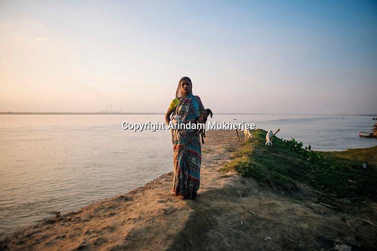 Rita Mondol with 2 of her goats stands on the eroded pathway of Kulidihar village. After the September 2014 erosion took away her home her only material asset is a few cattle and a rundown shop. Murshidabad District, West Bengal, India.
