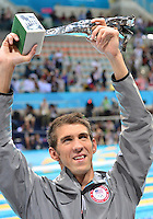 """August 04, 2012..Michael Phelps raises """"The Greatest Olympic Athlete of All Times"""" trophy awarded to him by FINA at the Aquatics Center on day eight of 2012 Olympic Games in London, United Kingdom."""