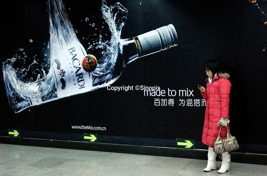 A lady checks her cell phone in front of BACARDI billboard in Beijing, China..