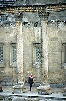 Man walking between columns at the Roman Theatre, Amman, Jordan.