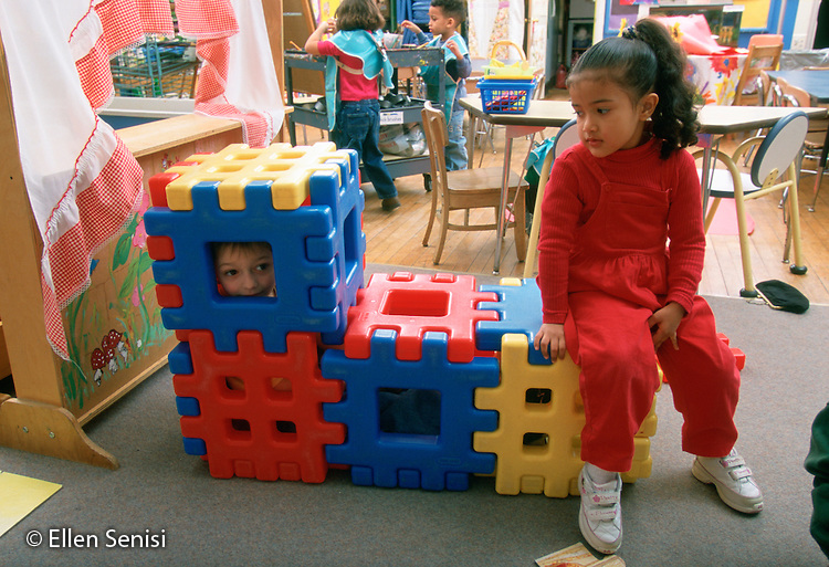 MR/ Schenectady, New York .Yates Arts-in-Education Magnet School/ Pre-Kindergarten.Boy hides in block structure as students play at free play time..(Foreground: boy, 5; girl: 4, Puerto Rican and Ecuadorian-American)..MR:Lup1, Kac1      FC#:25163-00202.scan from slide   .© Ellen B. Senisi